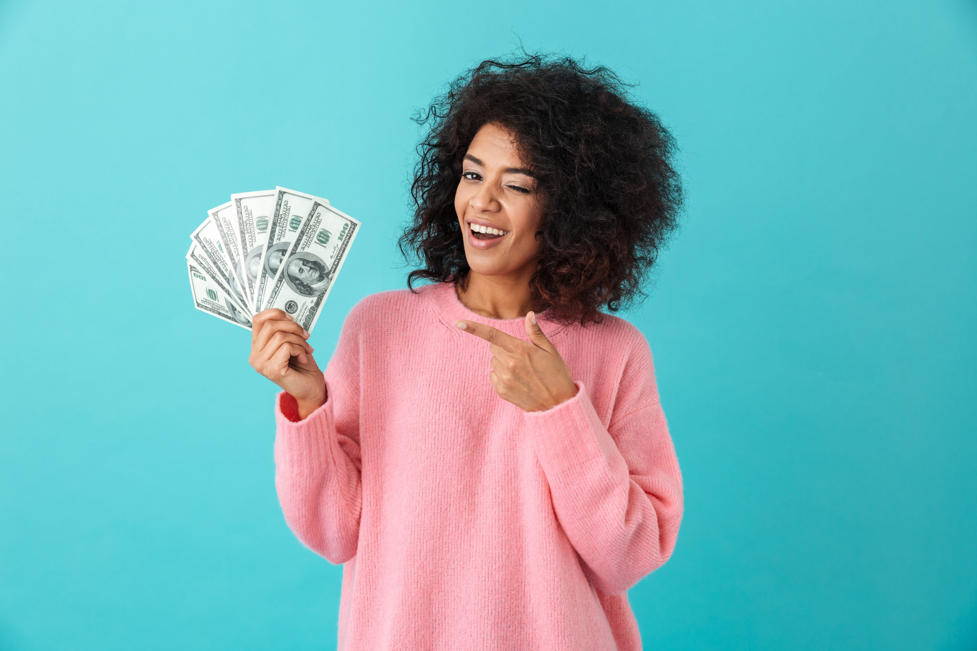 Portrait of american successful woman 20s with afro hairstyle holding lots of money dollar banknotes, isolated over blue background